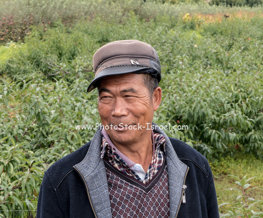 Portrait of a Chinese man wearing a Mao cap, Lijiang, Yunnan Province, People's Republic of China