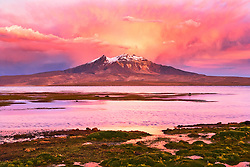Lago Chungara with a snow-capped mountain beneath a colorful cloud in background, Chilean Andes, Chile, South America