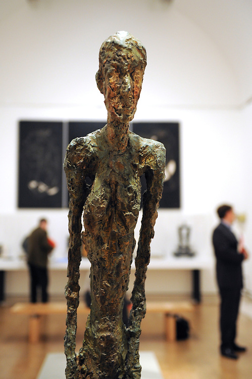 London.  September 30, 2008.  'Walking Man I,' a  Giacometti sculpture stares ahead as museum goers admire works from the Miro, Calder, Giacometti, Braque exhibition at the Royal Academy of Arts.  The show opens on October 4 and runs until January 2, 2009.
