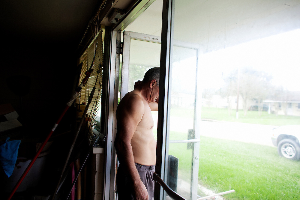 Julius Gaudet, 62, stand in the doorway of his garage after a day of hunting alligators near Shell Island, Louisiana on September 19, 2009.