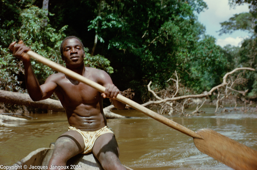 Man paddling canoe on Hana River in Tropical Rain Forest, western Ivory Coast, Africa.