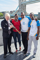 Image ©Licensed to i-Images Picture Agency. 06/06/2014. London, United Kingdom. Mayor of London Boris Johnson holds the Commonwealth Games Queen\'s Baton Relay with World and Commonwealth champion Christine Ohuruogu MBE (red), Michael Pusey (right) and Faramolu Johnson (far right) to the capital as part of the England led of a journey that will see it travel 190,000 kilometres over 288 days. City Hall, The Queen\'s Walk. Picture by Daniel Leal-Olivas / i-Images