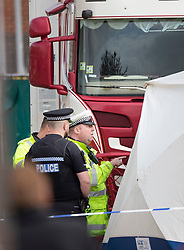© Licensed to London News Pictures. 23/10/2019. Grays, UK. Police officers gather at the front of a truck at Waterglade Industrial Park in Grays, Essex where the bodies of 39 people have been found. The driver, a 25-year-old-man from Northern Ireland, has been arrested on suspicion of murder. . Photo credit: Peter Macdiarmid/LNP