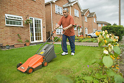 Older man cutting the grass in his garden,