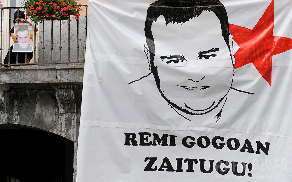 "An unidentified woman hangs a portrait of Remi Aiestaran, ANV member and Villabona town councillor, in the balcony of the northern Spanish Basque village of Villabona, on August 6, 2009. Aiestaran had a heart attack after clashing with Basque police during a pro ETA imprisoned members protest, on July 31, 2009. Banner reads in Basque ""Remi we remember you"". PHOTO/Rafa Rivas"