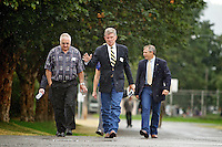 Orin Moses, left, walks in the rain Wednesday toward the Spirit Lake Senior Center with Gov. Butch Otter while the two discuss emergency medical service for the area.