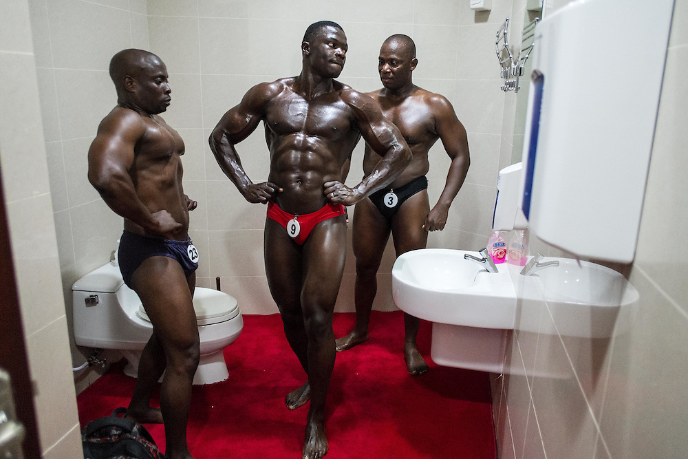 Dar es Salaam, Tanzania - 2015-08-29  -  Contestants prepare in the VIP toilet moments before the Most Muscular Man Tanzania competition in Dar es Salaam, Tanzania on August 29, 2015.  Photo by Daniel Hayduk