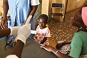 Kambou Sansan, 4, a malnourished boy,  and his caretaker Kambou Lononbeni listen to a health worker during a visit at the Panzarani health center in the village of Panzarani, Zanzan region, Cote d'Ivoire on Friday November 25, 2011. The woman takes care of Sansan since his mother died.