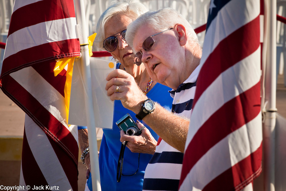 "10 SEPTEMBER 2011 - TEMPE, AZ:     Visitors to the ""Healing Field"" in Tempe, AZ, look at note cards that memorialize people killed on the Sept 11, 2001, terrorists attacks. The ""Healing Field,"" a display of 2,996 flags, one for each person killed in the September 11 terrorists attacks on the World Trade Center in New York City and Washington DC, have become an annual tradition in Tempe. The event is sponsored by the National Exchange Club.     PHOTO BY JACK KURTZ"