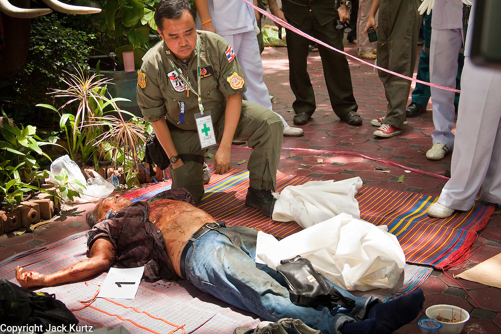 "20 MAY 2010 - BANGKOK, THAILAND: Medical workers and forensics experts recover the bodies of nine anti government protesters in Wat Pathumwanaram near the Ratchaprasong Intersection in Bangkok Thursday. At least some of the nine were so called ""Black Shirts"" armed fighters who support the Red Shirts. The day after a military crackdown killed at least six people, Thai authorities continued mopping up operations around the site of the Red Shirt rally stage and battle fires set by Red Shirt supporters in the luxury malls around the intersection. They also recovered at least seven bodies from Wat Pathumwanaram, next to Central World mall, which was destroyed by fire. The nine people killed in the temple were not included in the government's body count from Wednesday.    PHOTO BY JACK KURTZ"