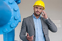 Young male manager using smart phone in industry