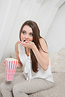 Young woman eating popcorn while sitting on bed
