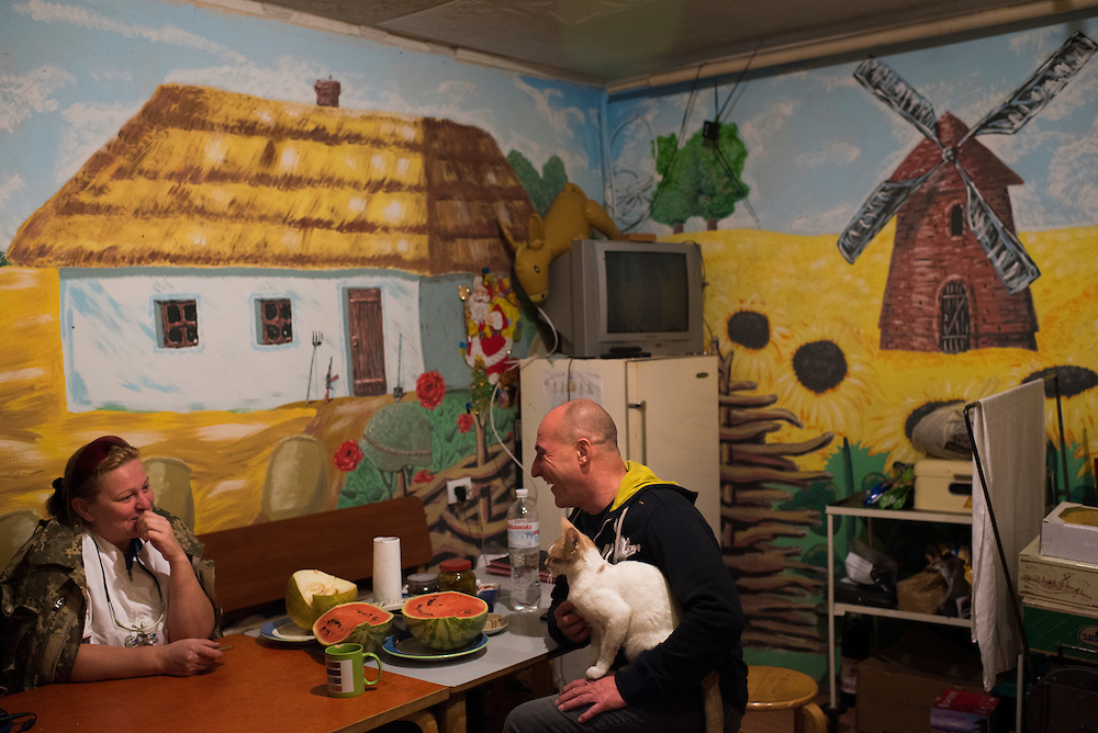 Volunteer dentist Alla talks with Ukrop Dental founder Igor Yaschenko on September 20, 2016 in Karlivka, Ukraine about 12km from the front line. The mural on the kitchen wall is a pastoral scene that includes a Kalashnikov-style rifle leaning against a house.