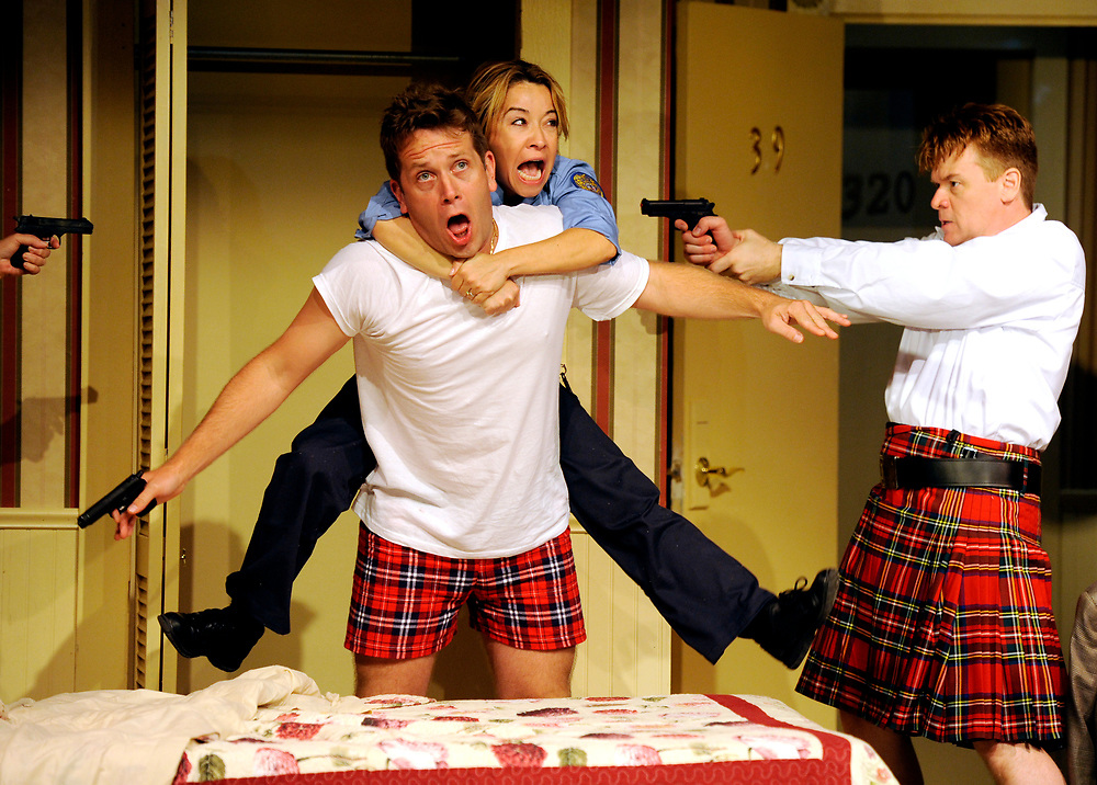 "Jennifer Cody playing Billie Dwyer jumps out of the closet on to Jeremy Webb playing Todd with John Scherer as Eric Sheridan pointing a gun in the background during a run-through of ""Unnecessary Farce"" at the Cape Cod Playhouse."