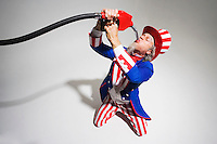 Uncle Sam on his knees sucking on a gasoline nozzle..Model Release: 20080626_MR_A