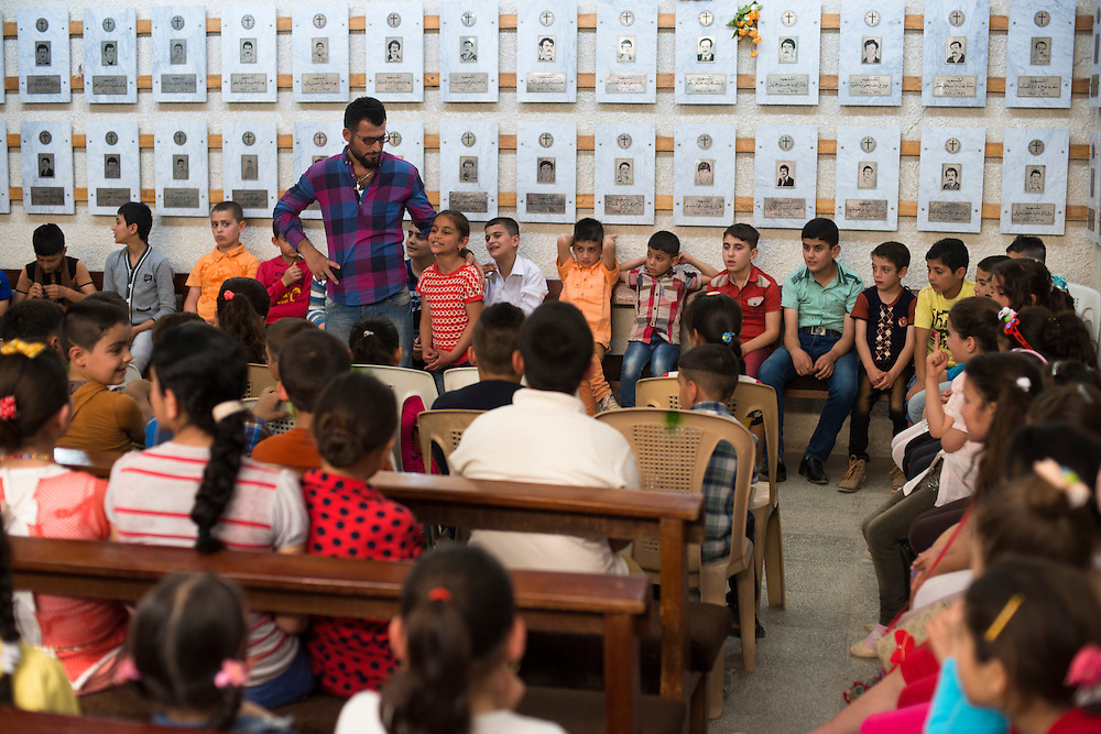 Children at the Saint Yohana Church in the Christian town of Karaqosh are taught Catechism classes in a room lined with memorial plaques honoring Christians from the community who were killed during the Iran-Iraq war and subsequent conflicts. Located on the Nineveh Plain, the cradle of Christianity in Iraq, Karaqosh is the country's largest Christian city. It lies just 20 kilometers from Mosul, one of the most violent cities in Iraq and the scene of numerous attacks against the Christian population. Karaqosh, Iraq. 18/04/2014.