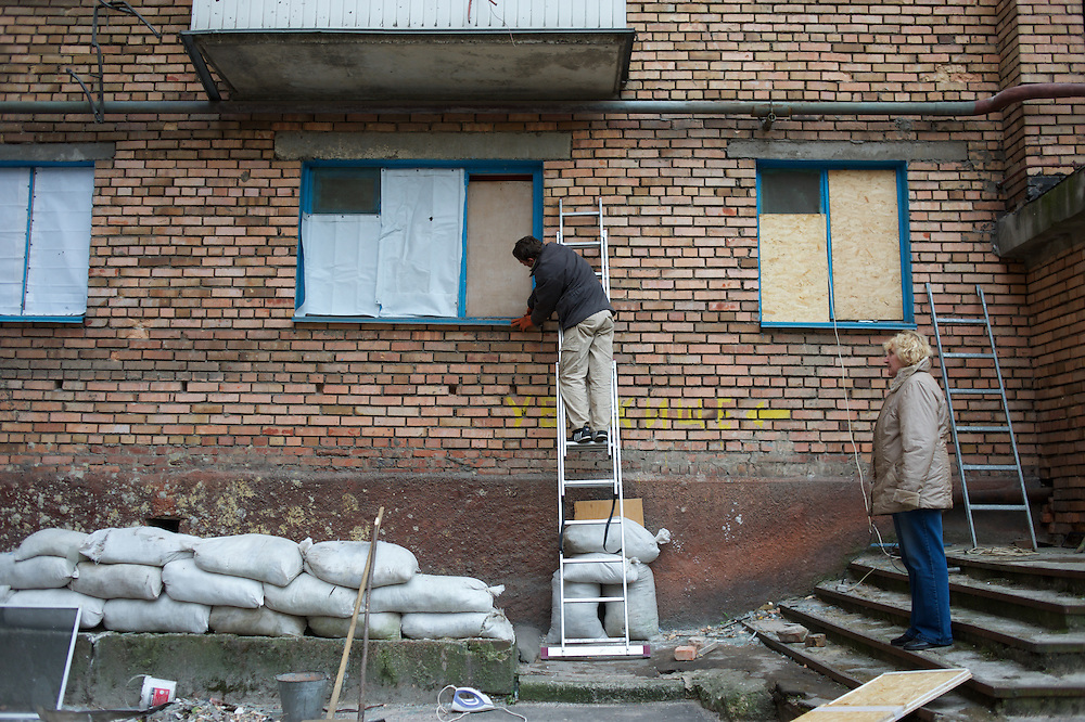 DONETSK, UKRAINE - OCTOBER 19, 2014: Local residents repair the windows of their apartment in a residential area of central Donetsk. Shellfire from Ukrainian National Guard and the DNR rebels, fighting for the control of strategic positions around Donetsk, have in the past months indiscriminately hit residential areas in the city, claiming destruction and fatalities among the civilian population. CREDIT: Paulo Nunes dos Santos