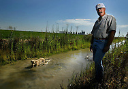 Bruce Rolen and his dog Bobo stand next to Rolan's rice field in Williams, CA. Rolen is a farmer who profited from selling his water last year.