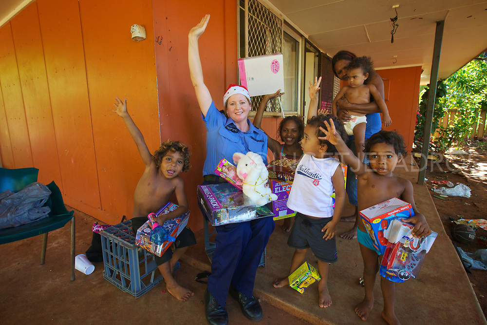 Children and a police woman cheering and posing after a present drop. The Broome Police & Community Centres (PCYC) organise a present drop each year to bring festive spirit to unprivileged children of Broome, WA