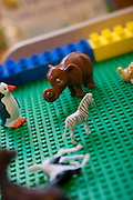 A toy elephant, penguin and zebra, on a green background.