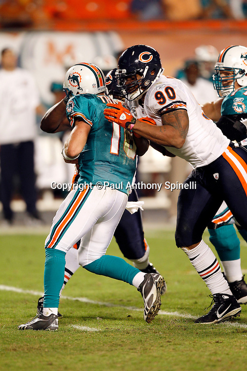 Miami Dolphins quarterback Tyler Thigpen (16) gets hit by Chicago Bears defensive end Julius Peppers (90) and Chicago Bears defensive tackle Tommie Harris (91) during the NFL week 11 football game against the Chicago Bears on Thursday, November 18, 2010 in Miami Gardens, Florida. The Bears won the game 16-0. (©Paul Anthony Spinelli)