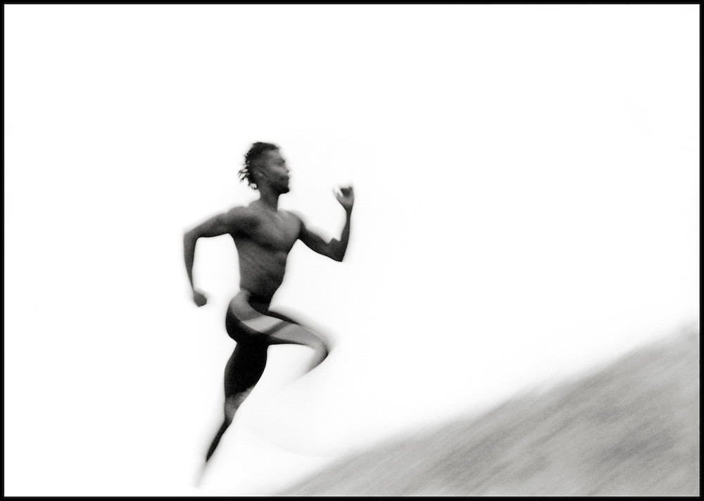 Young man running uphill (B&W sepia, blurred motion)