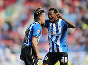 Tim Chow scores to make it 1-0 to Wigan Athletic and celebrates with Wigan Athletic defender Gaetan Bong during the Sky Bet Championship match between Wigan Athletic and Brighton and Hove Albion at the DW Stadium, Wigan, England on 18 April 2015.