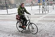 Een man fietst op weg naar zijn werk door de sneeuw
