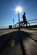 A man pushing his bicycle along Eastbourne Pier is silhouetted against a cloudless blue sky.