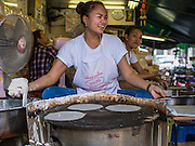 """03 APRIL 2014 - BANGKOK, THAILAND:  A woman makes """"roti"""" a type of unleavened Indian flat bread in Khlong Toey Market. Roti is popular throughout Thailand and is used as starch for southern Thai curries (instead of rice) and a snack, filled with fruits (especially bananas) or sugar.  Khlong Toey (also called Khlong Toei) Market is one of the largest """"wet markets"""" in Thailand. The market is located in the midst of one of Bangkok's largest slum areas and close to the city's original deep water port. Thousands of people live in the neighboring slum area. Thousands more shop in the sprawling market for fresh fruits and vegetables as well meat, fish and poultry.     PHOTO BY JACK KURTZ"""