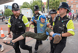 © Licensed to London News Pictures. 17/07/2019; Bristol, UK. Extinction Rebellion Summer Uprising 2019. A man with blue hair stuck his foot to the road and police worked to remove him safely. Police remove protesters arresting some and putting them in police vans as they try to clear a major road junction occupied by an Extinction Rebellion protest which has caused major traffic disruption. Campaigners locked themselves onto a pink bath tub, and held 7 minute roadblocks on other parts of the junction complex. Extinction Rebellion are holding a five-day 'occupation' of Bristol, by occupying Bristol Bridge in the city centre and traffic has to be diverted and carrying out other events. As part of a country-wide rebellion called Summer Uprising, followers will be holding protests in five cities across the UK including Bristol on the theme of water and rising sea levels, which is the group's focus for the South West. The campaign wants the Government to change its recently-set target for zero carbon emissions from 2050 to 2025. Photo credit: Simon Chapman/LNP.