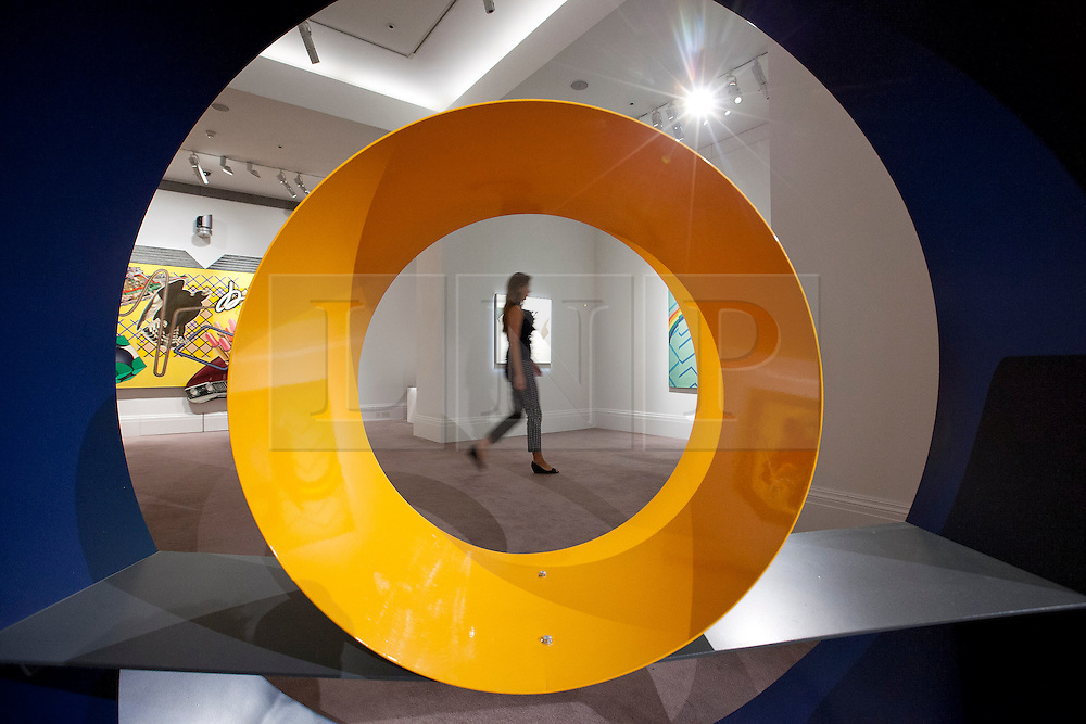 "© Licensed to London News Pictures. 03/09/2013. London, UK. A Sotheby's employee is seen through David Annesley's ""Untitled (Circle)"" (1966) during the press view for an exhibition of art from the 1960's at Sotheby's in London today (03/09/2013). The exhibition, entitled ""The New Situation: Art in London in the Sixties"" and located at the auction house's New Bond Street building, is open to the public from 4th to the 11th of September 2013. Photo credit: Matt Cetti-Roberts/LNP"
