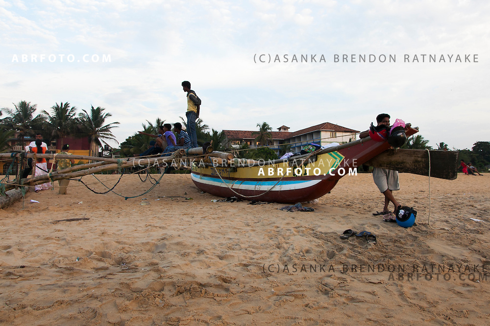 A docked traditional fishing boat on the Negombo beach, as fishermen rest on it waiting to go to sea. Negombo is a major city in Sri Lanka, located on the west coast of the island and at the mouth of the Negombo Lagoon
