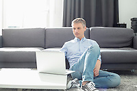 Full-length of man using laptop in living room