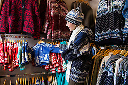 Woman in Eva handicraft shop in Tartu. Knitting, hand-made woolly cardigans.