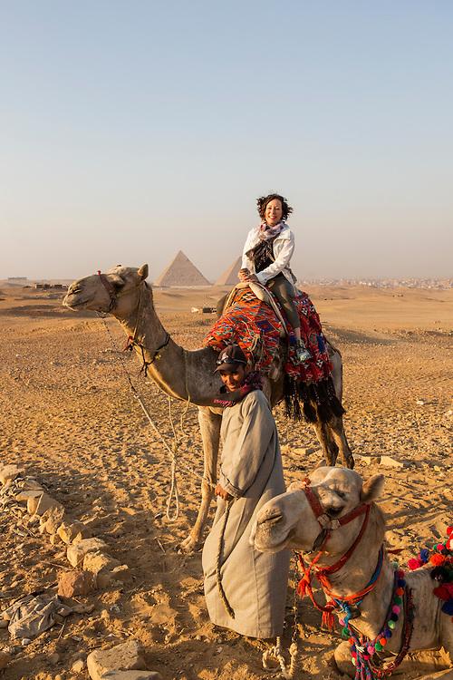 Egypt, Cairo, American tourist Janet Souders on camel safari in Sahara Desert near Great Pyramids of Giza at sunset