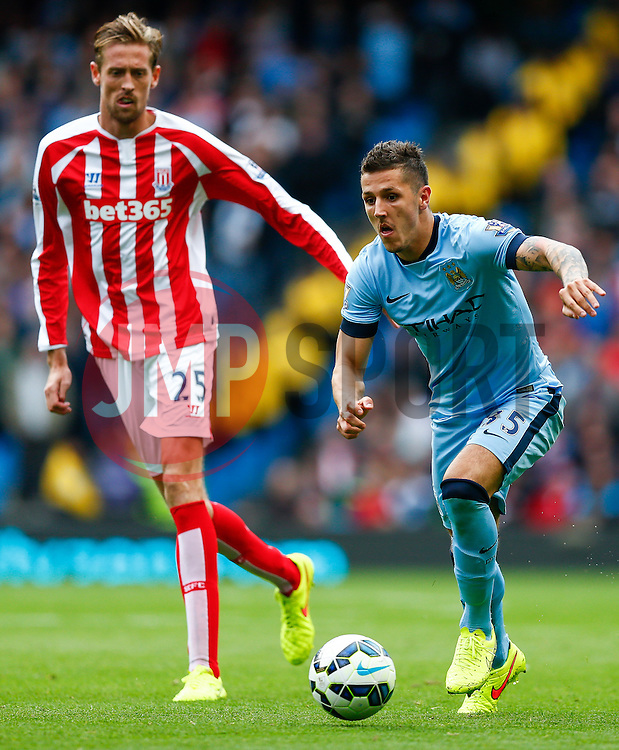 Stevan Jovetic of Manchester City is challenged by Peter Crouch of Stoke - Photo mandatory by-line: Rogan Thomson/JMP - 07966 386802 - 30/08/2014 - SPORT - FOOTBALL - Manchester, England - Etihad Stadium - Manchester City v Stoke City - Barclays Premier League.