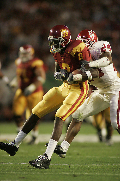 University of Southern California wide receiver Dwayne Jarrett catches a pass over Oklahoma University defensive back Marcus Walker during USC's 55-19 victory over OU on January 4, 2005 in the FedEx Orange Bowl at Pro Player Stadium in Miami, Florida.