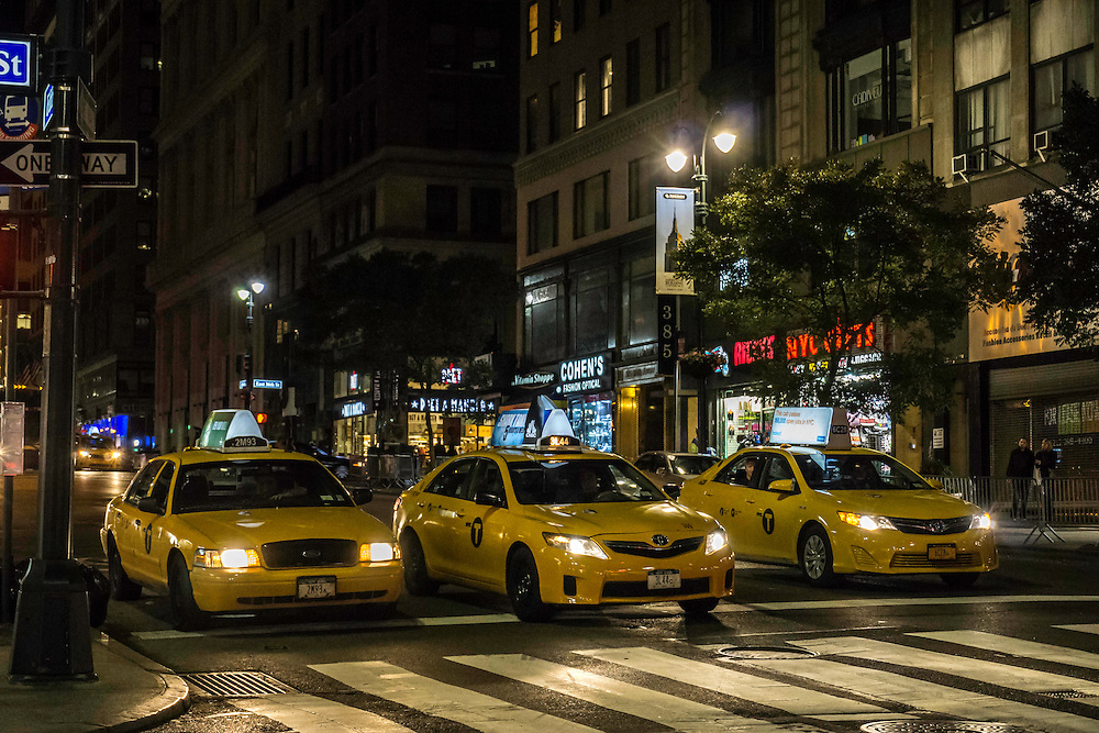 A line of taxi cabs waiting at a light in New York City (Manhattan) on a warm Fall night.