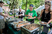 """From left: George Weckman, Dave Yuhas, and Stacie King serve themselves during a barbecue on the College Green on May 31, 2014. The event, for Ohio University alumni and their families, was part of the """"On The Green"""" weekend, which was hosted by the Ohio University Alumni Association. Photo by Lauren Pond"""
