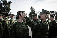 Two soldiers arrange their uniform before the first official parade at the military base in Rukla.