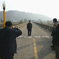 TUMEN, OCTOBER-26:  Chinese tourists take souvenir photos at the demarcation line between North Korea and China ,October 26,2006.