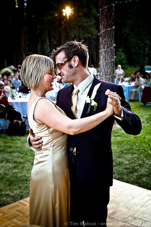 Newlywed husband and wife share a first dance at their outdoor wedding.