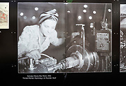 Public display of old historic images about the GWR works, Swindon, Wiltshire, England, UK - female worker machining a 25 pounder shell 1942