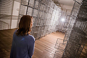 Light Sentence 1992 - Mona Hatoum a new Tate Modern exhibition. It presents around 100 works from the 1980s to the present day, including early performances and video, sculpture, installation, photography and works on paper. Mona Hatoum runs from 4 May to 21 August 2016.<br /> <br /> Highlights include:  Large-scale installations that fill entire rooms, including Impenetrable 2009, a suspended square formed of hundreds of delicate rods of barbed wire which hover above the floor, and Light Sentence 1992, in which walls of wire mesh lockers and a single lightbulb cast constantly moving shadows; Hot Spot 2013, a giant globe that uses red neon to outline the contours of the continents; a kinetic sculpture in which a rotating motor-driven arm draws circular lines across a large sandpit; and Homebound 2000, an installation of kitchen utensils and furniture which buzzes with electricity