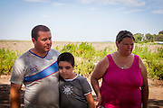 2014/11/18 - Monte Maiz, Argentina: Claúdio Fuentes (34) and Antónia Alaris (36) with their son Axel David Fuentes (8) in front of the soya field that faces their home in Monte Maiz. Their daughter, Antonella Fuentes, was diagnosed with osteosarcoma, a cancerous bone tumor, at the age of 6. She died a few months later.  The cases of cancer grew exponentially in the area since the introduction of glyphosate on the soy cultivation.  707 <br /> Cancer cases per 100,000 pepople were register by health researchers in the core area of soybean cultivation. These are three times as many  as the national average. (Eduardo Leal)