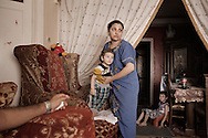 Egypt, Cairo: Mary, a coptic woman helps her son Jon to dress in her house in Moqattam,the christian coptic quarter in Cairo where live 40.000 Zabbaleen (garbage collectors). ph.Christian Minelli...