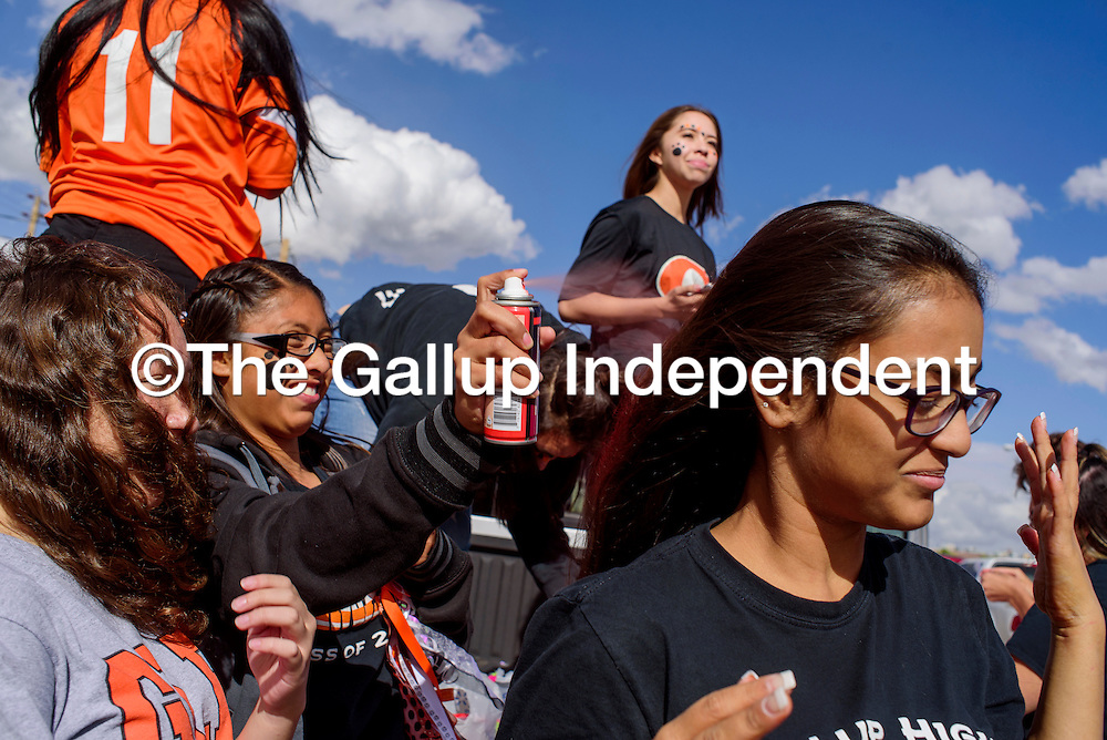 Jocelyn Retana, center, applies orange hair spray to her classmate Prina Patel's hair as they get ready to represent the sophomore class in Gallup High School homecoming parade Friday in Gallup.