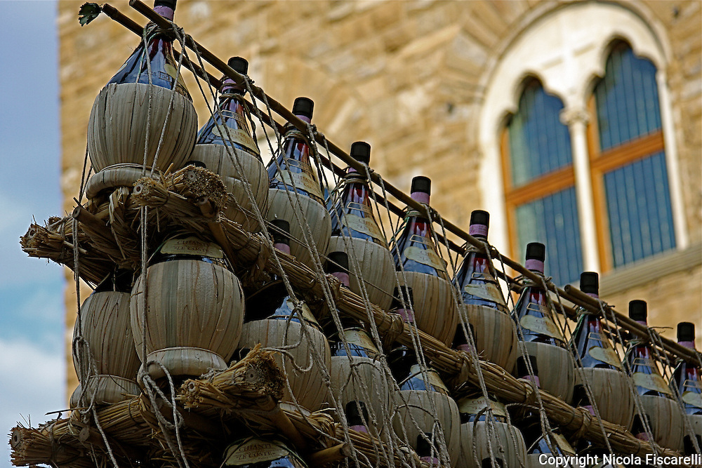 The traditional Chianti bottles full of wine  proudly  displayed during the wine festival in Florence-Italy.