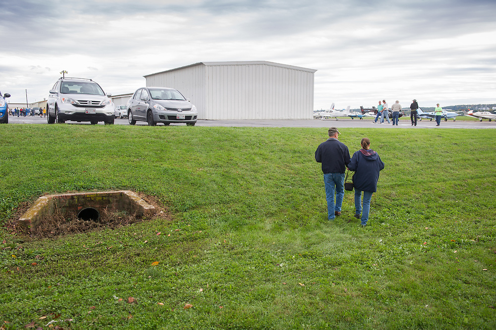 Couple walking up grassy hill towards small airplane hanger in Creswell, Maryland, USA